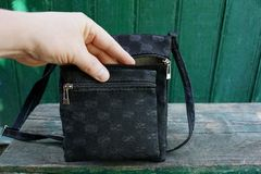 Hand in an open small black bag on a gray wooden bench Stock Photography