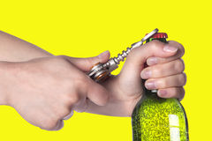 Hand opening beer bottle with metal opener. Hand holding and opening beer bottle with metal opener Royalty Free Stock Images