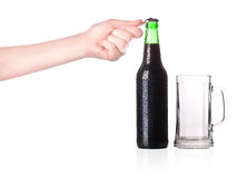 Hand opening beer bottle with metal opener Stock Photography