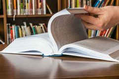 The hand opening and browsing the book pages Royalty Free Stock Images