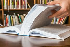 The hand opening and browsing the book pages Stock Image