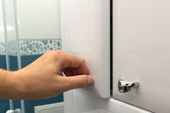 Hand opening a cabinet door Royalty Free Stock Image