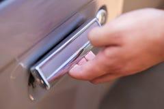 Hand opening car door Royalty Free Stock Image