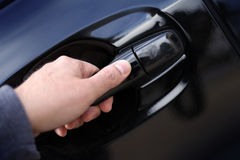 Hand opening a car door handle Royalty Free Stock Photography