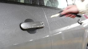 A hand opening car door with a key stock video