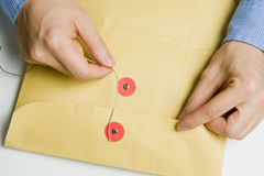 Hand opening confidential envelope Stock Image