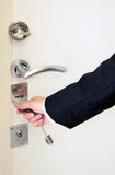 Hand opening door with key Stock Photography