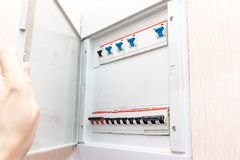 Hand opening electrical shield with automatic switches of electricity in the house - electricity control panel with circuit. Breakers stock photo