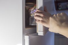 Hand opening fridge at night, diet fridge royalty free stock photo