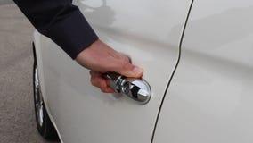 Hand opening white car door. Hand of white man grabs door handle of white car first then opening the door gently stock footage