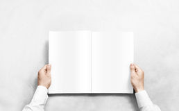 Hand opening white journal with blank pages mockup. Royalty Free Stock Photo
