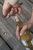 Hand opening a wine bottle with a corkscrew Royalty Free Stock Image