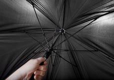 Hand opens big black umbrella Royalty Free Stock Photo