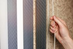 Hand opens black vertical blinds of fabric on the window. Close up.  royalty free stock photography