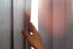 Hand opens black vertical blinds of fabric on the window. Close up.  stock images