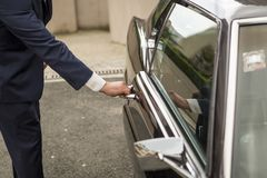 The hand of a man in a suit opens the door of a retro car. royalty free stock image