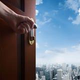 Hand opens door to the city Stock Images