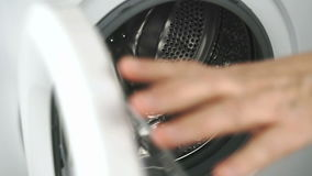 Hand opens a door of a washing machine. Close-up stock video