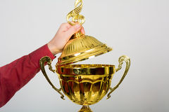 Hand opens the lid of the golden cup with a musical key Royalty Free Stock Photography