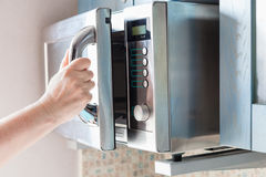 Hand opens microwave oven for heating food Royalty Free Stock Image