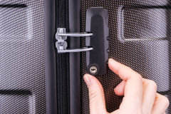 Hand opens suitcase combination lock. On the gray suitcase Royalty Free Stock Photo