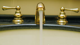 The hand opens the tap water in vintage washstand stock video footage