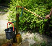 Hand operated water pump. Old hand operated water pump in action stock photo