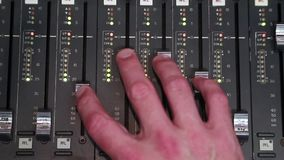 Hand operating Digital sound board used to mix audio. Sound mixer used for mixing audio and music for live events, concerts, festivals, broadcast television stock video