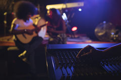 Hand operating sound mixer while musicians practicing in nightclub Stock Image