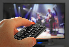 Hand operating tv remote control. Photo of a hand operating a television remote control device to change channels royalty free stock image
