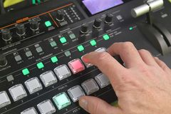 Hand operating Video production switcher used for live events. Hand operating Audio and video production switcher used for live events, in the audio video A/V royalty free stock images