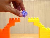 Hand opheffend die blok van brug van stuk speelgoed blokken wordt gemaakt Stock Afbeeldingen