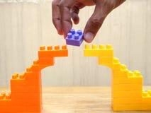 Hand opheffend die blok van brug van stuk speelgoed blokken wordt gemaakt Stock Foto