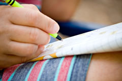In hand oplossende kruiswoordraadsels van de pen Stock Fotografie