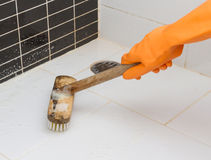 Hand in orange glove cleaning  bathroom dirty floor Royalty Free Stock Images