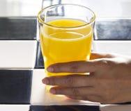 Hand with orange juice in sunshine, realistic Atmosphere Stock Photos