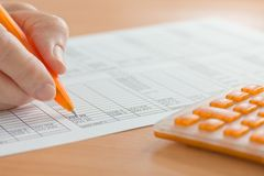 Hand with Orange Pen and Calculator Analyzing Spreadsheet Figures Stock Photography