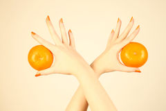 Hand with orange tangerine. Ripe mandarin in the woman's hands with orange nails Royalty Free Stock Photo