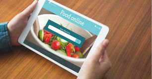 Hand ordering food on digital tablet with search screen on it royalty free stock photography