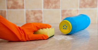 Hand in orenge rubber gloves wash the surface of the with a soft yellow sponge near the scratched detergent Royalty Free Stock Photography
