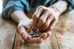 Hand oude mens die voor geld wegens de honger bedelen stock foto's