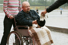 Hand out for invalid. Young man in wheelchair takes a handout from the stranger Royalty Free Stock Image