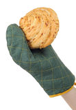 Hand in Oven Glove Holding Bun. A baker's hand in a green oven glove holding a fresh bun on a white background - vertical orientation Royalty Free Stock Photos