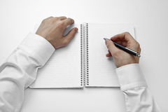 Hand over a blank book. Hand writing on a lined notebook Royalty Free Stock Photo