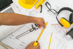Hand over Construction plans with yellow helmet and drawing tool Royalty Free Stock Photo