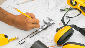 Hand over Construction plans with yellow helmet and drawing tool Royalty Free Stock Images