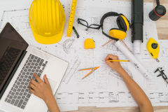 Hand over Construction plans with yellow helmet and drawing tool Stock Image