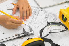 Hand over Construction plans with yellow helmet and drawing tool Stock Images