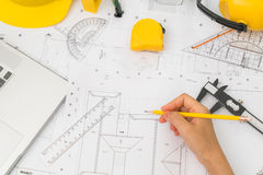 Hand over Construction plans with yellow helmet and drawing tool Stock Photography