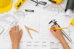 Hand over Construction plans with yellow helmet and drawing tool Royalty Free Stock Photos